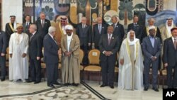 Arab leaders prepare to pose for a picture ahead of the opening session of the 23rd Arab League Summit, in Baghdad, Iraq, March 29, 2012.