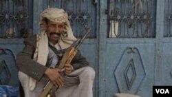 Seorang anggota suku Hashid siaga dengan senjatanya di ibukota Sana'a.