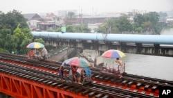 """Warga naik """"trolley"""", kereta yang dibuat oleh penduduk setempat sebagai alat transportasi dengan memanfaatkan jalur kereta api saat topan yang memicu hujan mulai mengguyur kota Manila, Filipina (17/10)."""