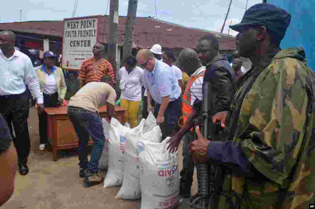 People hand out foodstuff donated by the U.S at the West Point area that has been hard hit by the Ebola virus in Monrovia, Liberia, Aug. 26, 2014.