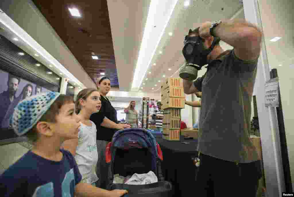 An Israeli man shows his children how to adjust a gas mask at a distribution point at a shopping mall in the West Bank Jewish settlement of Maale Adumim, near Jerusalem.