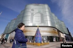 A woman walks past an Intime Lotte Department Store in downtown Beijing, China Jan. 10, 2017.