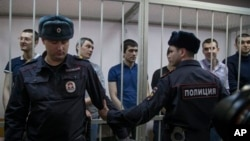 Defendants stand in courtroom cage, Moscow, Feb. 21, 2014.