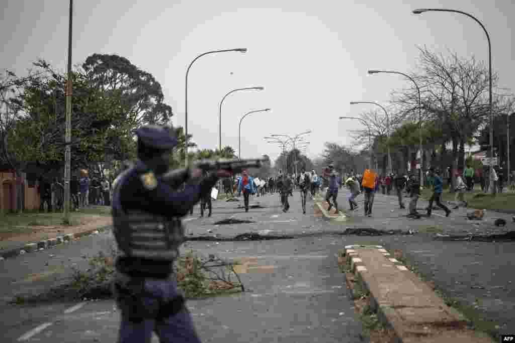 ប៉ូលិសកុបកម្មអាហ្វ្រិកខាងត្បូងឈរជើងតាមទីកន្លែង នៅពេលដែលបាតុករប្រឆាំងនឹងការរឹបអូសដី បញ្ហាផ្ទះសម្បែង និងបញ្ហាគ្មានការងារធ្វើ នៅក្នុងស្រុក Eldorado Park និងស្រុក Freedom Park នៅ ក្នុងក្រុង Johannesburg ប្រទេសអាហ្វ្រិកខាងត្បូង។