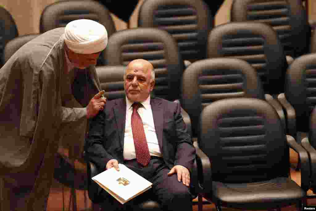 Shiite Sheikh Humam Hamoudi (left), Iraq's new deputy speaker of the Iraqi Council of Representatives, speaks with Iraq's incoming Prime Minister Haider al-Abadi as they attend a parliamentary session to vote on Iraq's new government at the parliament headquarters, Baghdad, Sept. 8, 2014.