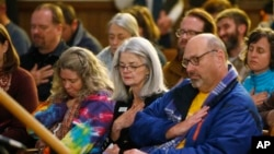 Planned Parenthood official Vicki Cowart, center, joins others in putting their hands on their hearts at All Souls Unitarian Universalist Church in Colorado Springs, Colo., during a vigil for victims of Friday's shooting at a Planned Parenthood clinic, Nov. 28, 2015.