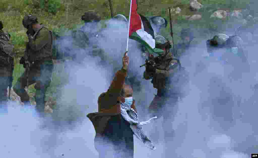 A Palestinian protester raises a national flag as a member of the Israeli forces points his gun, amid smoke from tear gas, during a demonstration against the establishment of Israeli outposts on their lands, in Beit Dajan, in the occupied West Bank.