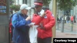 Duta kota Wayne Alexis membantu menunjukkan arah kepada seorang wisatawandi Union Square, San Francsico, California.