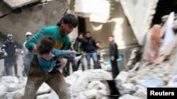 Seorang pria menyelamatkan seorang anak yang terluka dari rerntuhan bangunan di wilayah Al-Sukkari, dekat Aleppo, pasca serangan pasukan pemerintah suriah (2/2).