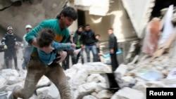 2月2號阿薩德軍隊轟炸阿勒頗,一名男子懷抱從瓦礫下挖出的一名受傷的孩子。