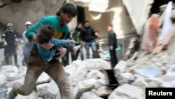 A man carries an injured child who was taken out from under debris at a site after what activists said was shelling by forces loyal to Syria's President Bashar al-Assad in Al-Sukkari neighbourhood in Aleppo, Feb. 2, 2014.