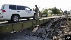 Mobil yang mengangkut tim forensik dan anggota OSCE dalam misi mereka di Ukraina melewati sebuah jembatan yang rusak di Debaltsevo, Ukraina timur (3/8/2014).
