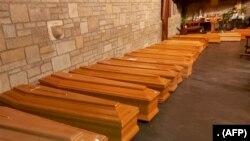 Deretan peti jenazah korban meninggal akibat virus corona di sebuah kapel di Bergamo, Lombardy, Italia, sebelum dikirim ke kremasi. (Foto: ANSA/AFP)