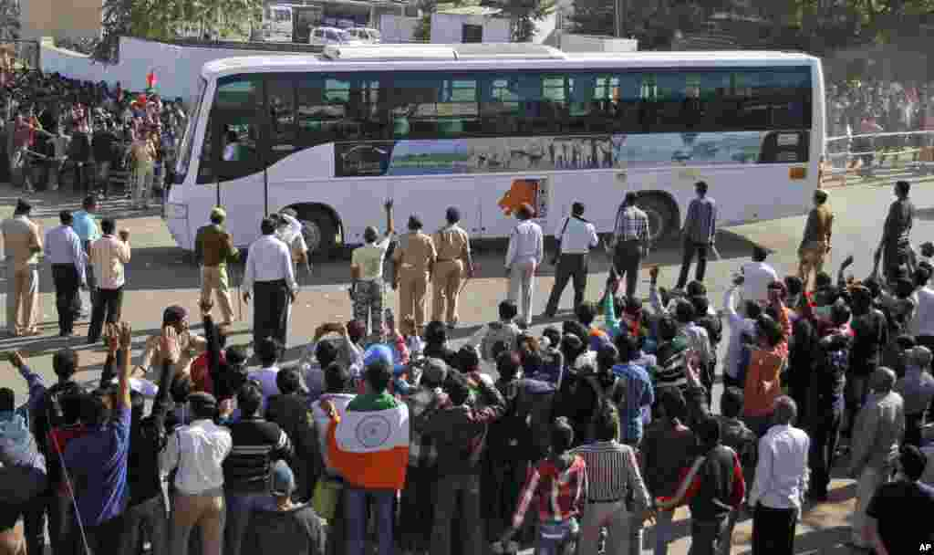 Indian cricket fans wave towards a bus carrying Pakistani cricket players, outside the Sardar Patel Stadium, December 28, 2012.