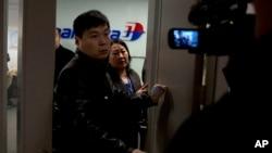 一名马航工作人员试图赶走聚集在北京国际机场马航办事处外的记者。(2014年3月8日)