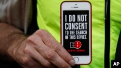 FILE - A man holds up his iPhone during a rally in support of data privacy outside an Apple store in San Francisco, Calif.