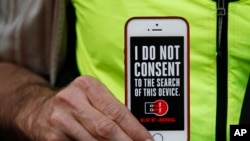 A man holds up his iPhone during a rally in support of data privacy outside an Apple store in San Francisco, Calif., Feb. 23, 2016. Protesters lashed out at a government order requiring Apple to help unlock an encrypted iPhone.