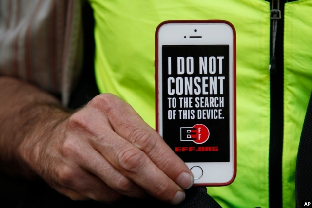 FILE - A man holds up his iPhone during a rally in support of data privacy outside an Apple store in San Francisco, Calif., Feb. 23, 2016. Protesters lashed out at a government order requiring Apple to help unlock an encrypted iPhone.