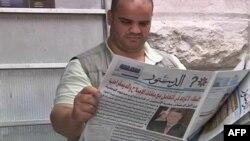 Jordanac čita u dnevnim novinama o napadu na kralja Abdulu