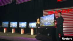 Models show a ICC Purios Ultra HD television at a Sharp news conference during the Consumer Electronics Show (CES) in Las Vegas January 7, 2013. Seen in the background are new Aquos 8-Series televisions and a 90-inch LED Smart 3D TV (far left). Sharp