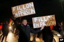 "A demonstrator holds placards reading ""Fillon in jail' ahead of the French conservative presidential candidate Francois Fillon's campaign rally in Compiegne, north of Paris, Feb. 15, 2017."