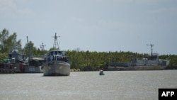 Myanmar navy ships are seen near Hainggyi Island, where a boat crammed with more than 700 migrants was taken, May 30, 2015.