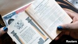 Une femme montre les passeports de sa famille avec un visa américain à Accra, au Ghana, le 1er février 2019. Le Ghana n'est pas inclus dans le programme de garantie monétaire.