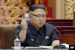 In this image made from video released by North Korean broadcaster KRT April 11, 2017, North Korean leader Kim Jong Un holds up the Supreme People's Assembly card in Pyongyang, North Korea.
