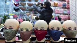 FILE - A vendor arranges a shelf full of masks as he waits for customers in a shopping mall in Yiwu, Zhejiang province, China.