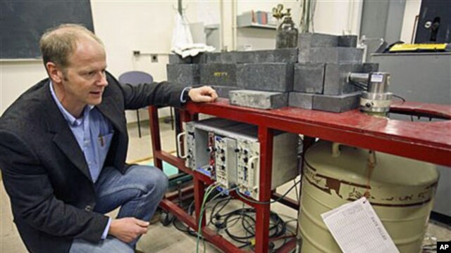 Professor Kai Vetter of the Department of Nuclear Engineering at the University of California at Berkeley kneels beside a germanium detector which is used to identify radioactive airborne particulates in a filter taken from air samples in Berkeley, Califo