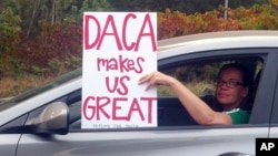 An unidentified woman holds a sign as she drives through rush hour traffic in Portland, Ore., Sept. 5, 2017. President Donald Trump Tuesday began dismantling the Deferred Action for Childhood Arrivals, or DACA, program, the government program protecting