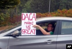 FILE - An unidentified woman holds a sign as she drives through rush-hour traffic in Portland, Ore., Sept. 5, 2017.