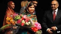 Malala Yousafzai menerima karangan bunga setelah berbicara kepada media di Birmingham, Inggris pasca pengumuman hadiah Nobel Perdamaian 2014, Jumat (10/10).