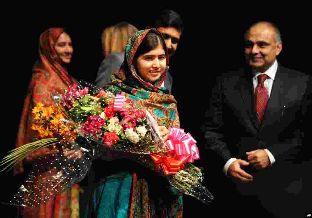 Malala Yousafzai holds flowers after speaking during a news conference at the Library of Birmingham, in Birmingham, England, after she was named as winner of The Nobel Peace Prize. The Prize was awarded jointly to Yousafzai of Pakistan and Kailash Satyarthi of India, for risking their lives to fight for children's rights.