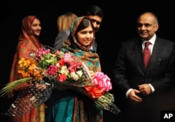 FILE - Malala Yousafzai holds flowers after speaking during a media conference at the Library of Birmingham, in Birmingham, England, Oct. 10, 2014, after she was named as winner of The Nobel Peace Prize.
