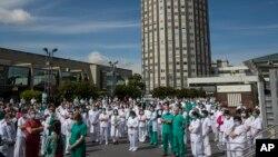 Para petugas medis mengheningkan cipta untuk dr. Joaquin Diaz, yang meninggal akibat Covid-19, di Madrid 20 April 2020.