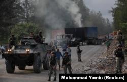 Polisi dan pasukan keamanan terlihat di dekat kendaraan yang dibakar oleh para pekerja perusahaan pertambangan raksasa A.S. Freeport McMoran Inc selama perselisihan perburuhan di Timika, Papua, 19 Agustus 2017. (Foto: REUTERS/Muhammad Yamin)