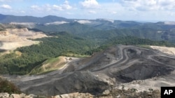 FILE - Coal trucks and heavy equipment look like children's toys on the Middle Ridge surface coal mine in southern West Virginia, Sept. 26, 2017.
