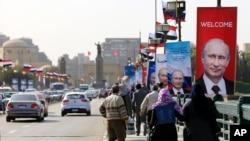 Poster-poster Presiden Rusia Vladimir Putin dipasang di Jembatan Qasr El Nile Bridge di Kairo, Mesir (9/2). (AP/Hassan Ammar)
