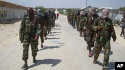 FILE - Members of Somalia's al-Shabab militant group patrol on the outskirts of Mogadishu, March, 5, 2012. Analysts say that the fight against the insurgency may be moving into the north of the country, to regroup in the semiautonomous region of Puntland after coming under heavy pressure from three foreign armies in southern Somalia.