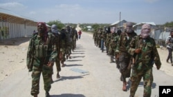 FILE - Members of Somalia's al-Shabab militant group patrol on the outskirts of Mogadishu, March, 5, 2012. An attack Thursday by African Union and Somali forces left at least 57 members of the extremist group dead.