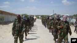 FILE - Members of Somalia's al-Shabab militant group patrol on the outskirts of Mogadishu, March, 5, 2012.