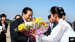 朝鲜中央新闻社的图片显示2010年10月周永康访问朝鲜在平壤机场接受鲜花