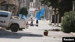 ປະຊາຊົນຖືຄຸ ໃນຂະນະທີ່ພວກເຂົາເຈົ້າຍ່າງຜ່ານຖະໜົນທີ່ໄດ້ຮັບຄວາມເສຍຫາຍ ໃກ້ກັບຜ້າສີຟ້າທີ່ຖືກໃຊ້ເປັນບ່ອນລີ້ຈາກດັກຍິງ ຫຼື snipers ໃນເມືອງ Manbij, ບໍລິເວນຂອງນະຄອນຫຼວງ Aleppo ທີ່ຄວບຄຸມໂດຍລັດຖະບານ. ຊີເຣຍ. 7 ສິງຫາ, 2016.