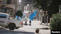 阿勒颇居民上街打水,他们在街上挂上蓝布,以防止狙击(2016年8月7日)