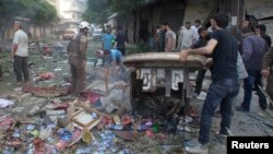 People inspect the damage at a market hit by airstrikes in Idlib city, Syria, June 5, 2016.
