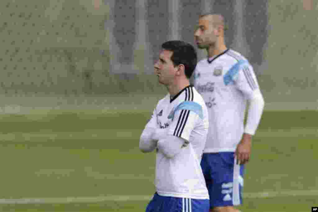 Argentina's Lionel Messi, left, and Javier Mascherano walk during a training session in Vespesiano, near Belo Horizonte, Brazil, Thursday, July 10, 2014. On Sunday, Argentina faces Germany for the World Cup final soccer match in Rio de Janeiro. (AP Photo/