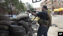 Milisi Sunni berlindung di balik ban-ban mobil dalam bentrokan antara pendukung dan penentang al-Assad di kota Tripoli, Libanon, (13/5).