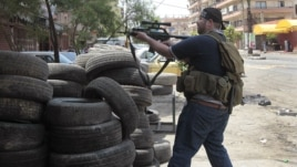 A Sunni gunman fires his weapon during clashes on Syria Street which divided the areas between Sunnis and Alawites, in the northern port city of Tripoli, Lebanon, May 13, 2012.