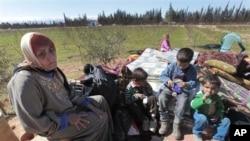 一位从叙利亚霍姆斯地区逃出的妇女带着她的几个孩子在黎巴嫩与叙利亚交界的地区(资料照片)
